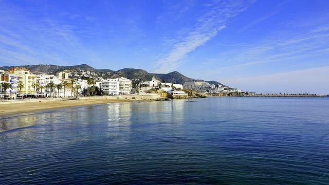 Der Strand von Sitges mit dem Dorf im Hintergrund
