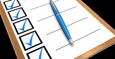 eine Mappe mit einem Blatt auf dem fünf Vierecke untereinander mit Linien daneben sind jeweils ein Häckchen darin und mitten auf dem Blatt liegt ein blauer Kugelschreiber