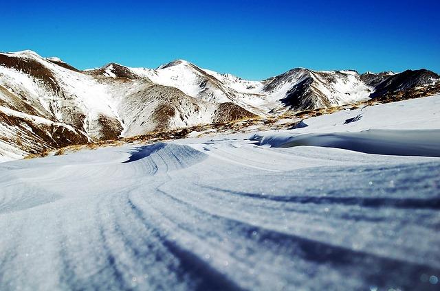 eine Schneepiste mit verschneiten Bergen im Hintergrund