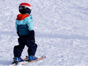 ein kleines Kind mit Helm und Skianzug das auf einer Schneepiste Ski fährt