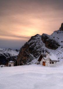 Sonnenuntergang in den Bergen, viel Schnee und zwei vereinzelte kleine Häuser