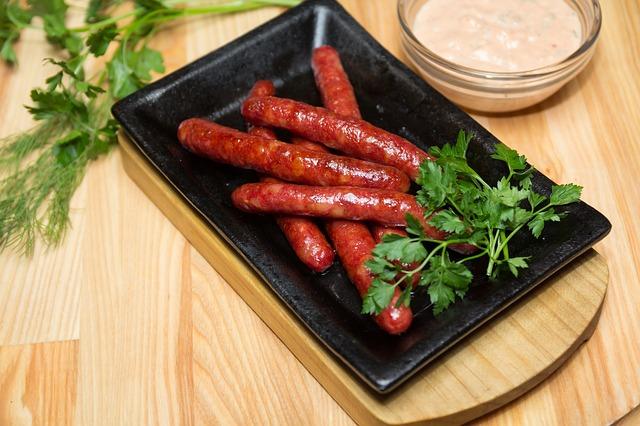 ein schwarzer rechteckiger Teller auf dem sechs Butifarras mit etwas Petersilie an der Seite liegen, daneben eine kleine Glasschüssel mit einer weissen Sauce