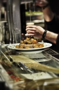 Tresen einer Bar mit Einem Teller voller Würstchen und Gemüse und im Hintergrund schenkt ein Kellner gerade ein Bier ein