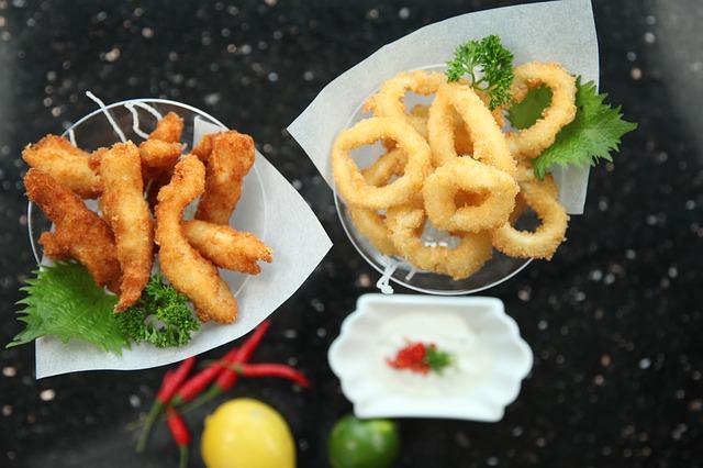 Auf einem schwarzen Tisch werden in verschiedenen kleinen Schalen frittierte Tapas presentiert, daneben liegt eine Zitrone, eine Limette, rote Chilischoten und ein Schüsselchen mit Alioli