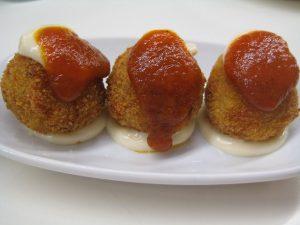 Drei runde Koquetten auf einem kleinen ovalen weissen Teller aufgeregt mit weisser sosse darunter und roter sosse darüber