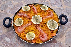 eine Paellapfanne mit Paella die mit grossen Garnellen und Zitronenscheiben dekoriert ist