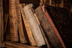 Ausschnitt eines Bücherregals mit alten und etwas zerfransten Bücher die etwas gekippt sind