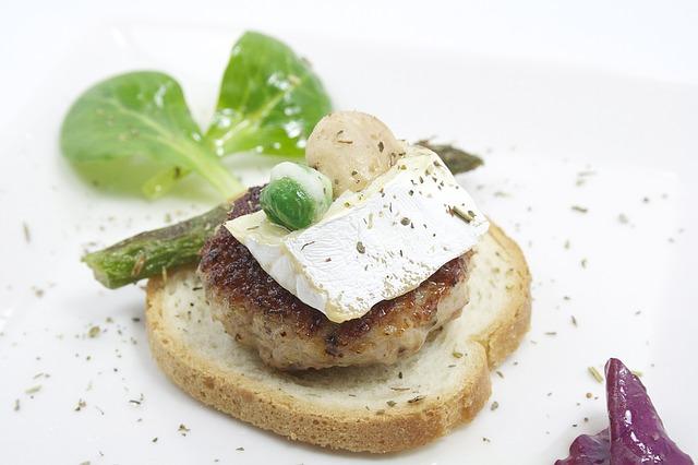 ein Zwieback mit einem Fleischbällchen darauf dekoriert mit einem grünem Spargel, Brie Käse und Rosenkohl