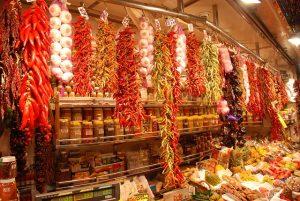 Ein Gewürzstand in der Boqueria mit einem Regal voller Gewürzgläser an der Wand und aufgehängte, getrocknete Paprika, Knoblauch, Chilis, und viel mehr