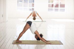 zwei Frauen die in einem weissen Saal mit Holzboden und grossen Fenstern auf ihren Matten Yoga praktizieren