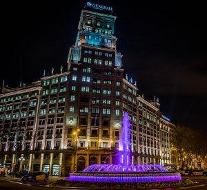 der Brunnen bei Nacht lila beleuchtet, links daneben ein gelb-schwarzes Taxi und dahinter das Generali Gebäude