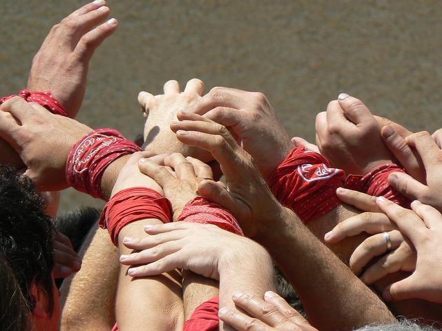 viele Arme von Catellers mit dem typischen roten Tuch um das Handgelenk gebunden, die sich aufeinander stützen