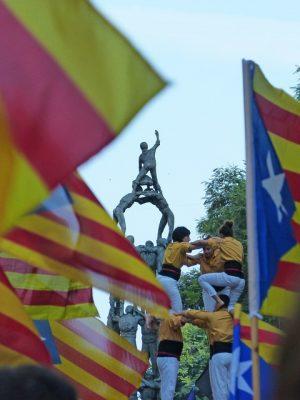 zwischen hoch erhobenen Unabhängikeitsflaggen Kataloniens sieht man eine Menschenpyramide mit castellers in gelben T-Shirts und dahinter ein Denkmal das eine fertige Menschenpyramide ist