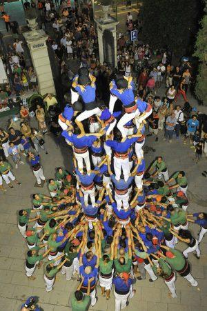 eine fast fertige Menschenpyramide, die Castells in weissen Hosen und blauen und grünen T-Shirts