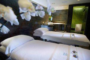 Raum mit dunkeln Wänden, zwei nebeneinander stehende Massagebetten mit weissen Handtüchern und eine Weisse Orchidee