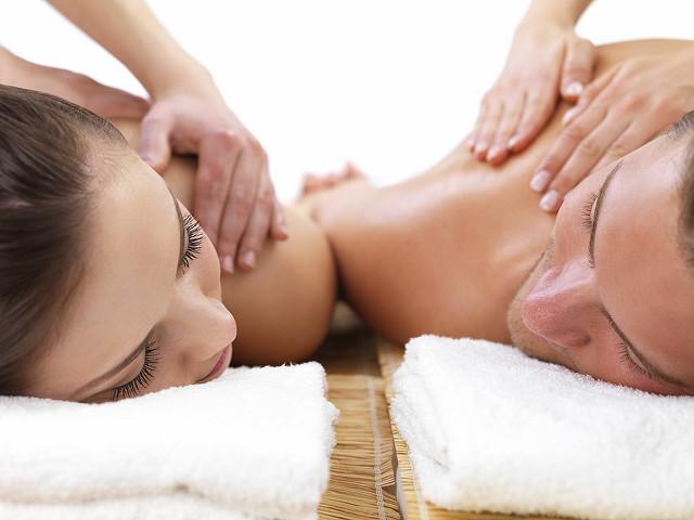 Ein Pärchen die eng nebeneinander liegen während sie eine Massage bekommen