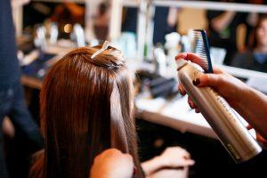 in einem Friseursalon werden jemandem hellbraune lange Haare mit Haarspray und einem schwarzem Kamm frisiert