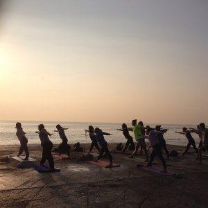 eine Yogaklasse mit zirka 14 Teilnehmern am Strand von Barceloneta bei Sonnenaufgang
