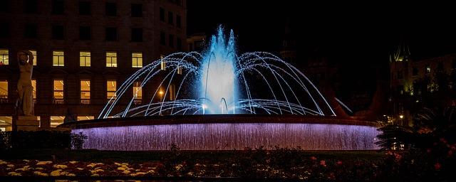 Der Brunnen bei Nacht bit weisser Beleuchtung man sieht die Lichter in den Fenstern des Gebäudes dahinter