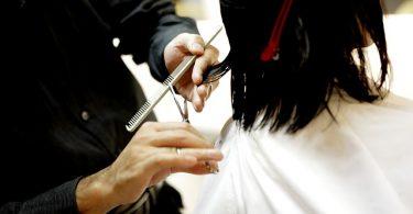 man sieht zwei Hände eines Friseurs in der rechten die Schere in der linken ein Kamm es werden gerade schwarze halblange haare geschnitten