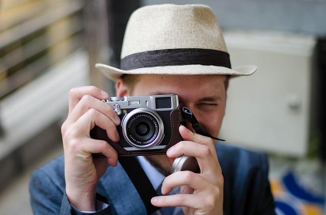 Ein junger Mann mit hellem Hut der gerade mit seiner Vintagekamera ein Foto von dir macht