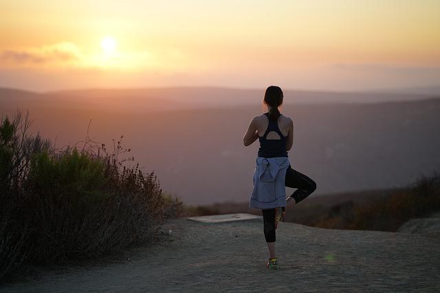 Eine Frau in der Position des Baums auf einem Berg während eines Sonnenuntergangs