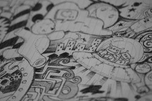ein liniertes Blatt gefüllt mit Bleistiftzeichnungen, unter anderem ein laufender Teddybär, ein Ufo mit zwei dreiäugigen Außerirdischen, eine Wolke, ein böse lachender Mond, Hochhäuser einer Grossstadt, Sterne, Planeten und andere Verzierungen