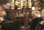 Foto eines Restaurants, zu sehen ist ein gedeckter Tisch, ein Stuhl aus Metal und eine gepolsterte Sitzbank unter einem grossen Spiegel in der man die Bar sieht