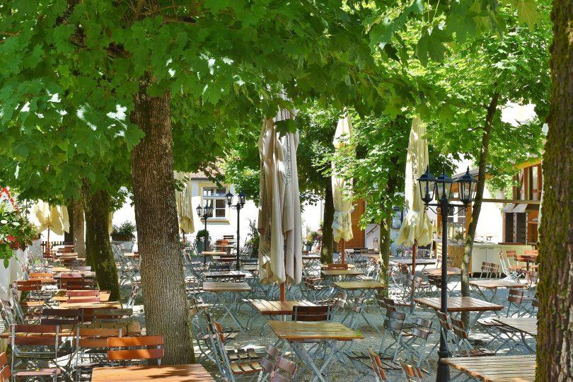 eine Terrasse eines Restaurant unter grünen Bäumen mit vielen leeren Klapptischen und Klappstühlen aus Holz und Metal
