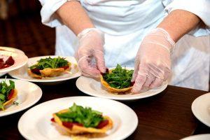Hände eines Kochs mit dünnen Gummihandschuhen bei der Vorbereitung kleiner Salate auf verschiedenen kleinen weissen Tellern