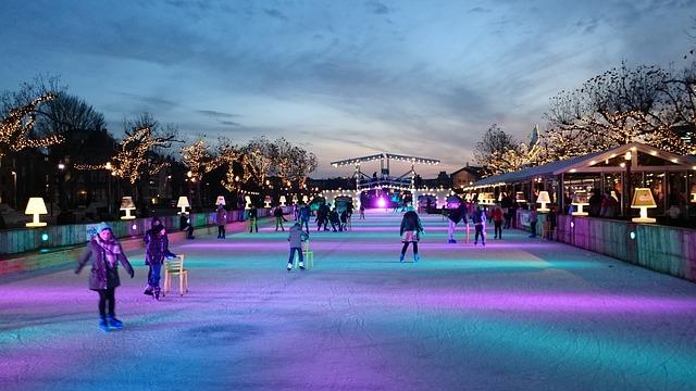 Eislaufbahn bei Dämmerung die grün und lila beleuchtet ist und auf der mehrere Menschen Schlittschuhfahren