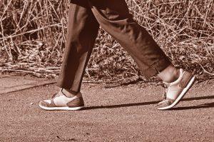 der untere Beine einer gehenden Person mit brauner Hose und Turnschuhen auf einem Gehsteig