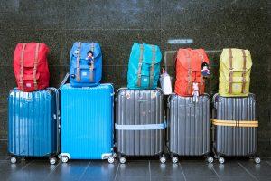 zwei blaue und drei graue Koffer in einer Reihe aufgestellt mit verschiedenfarbigen Rucksäcken darauf
