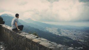 ein junger man mit schwarzer Hose und grauem T-Shirt der auf der Mauer eines hohen Bergs sitzt und auf die Stadt hinunter blickt