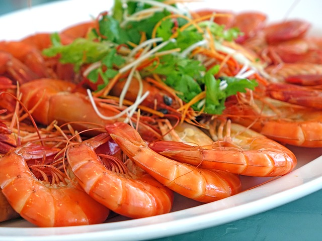 weisser ovaler Teller mit roten gekochten Garnelen schon aufgereiht und etwas Kresse oben drauf