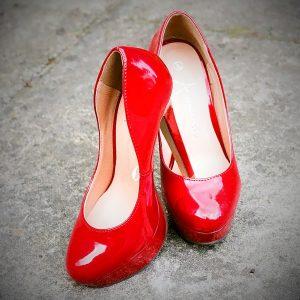 zwei nebeneinander gestellte rote high-heels auf einem Betonboden