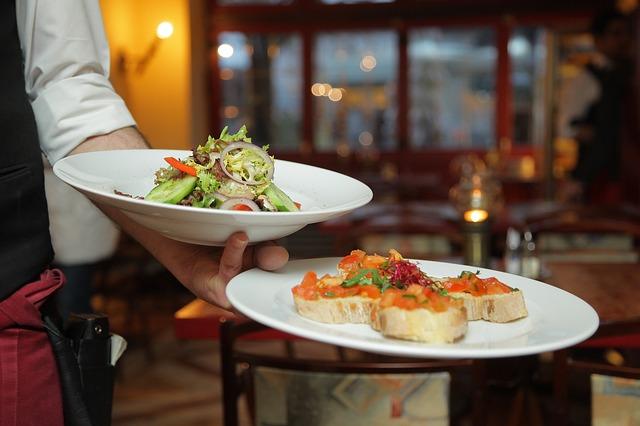 Arm eines Kellners der einen flachen weissen Teller mit Baguette und Tomate und einen tiefen Teller mit Salat in einem Restaurant hält