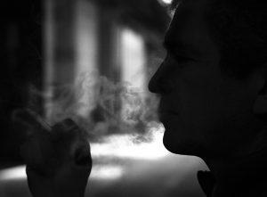 schwarz-weiss Foto einer Person die einen Joint raucht