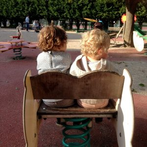 man sieht zwei kleine Kinder von hinten die zusammen auf einer kleinen Wippe sitzen