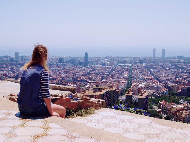 eine Frau die auf einer Treppe sitzt und die Aussichten auf die Stadt genießt