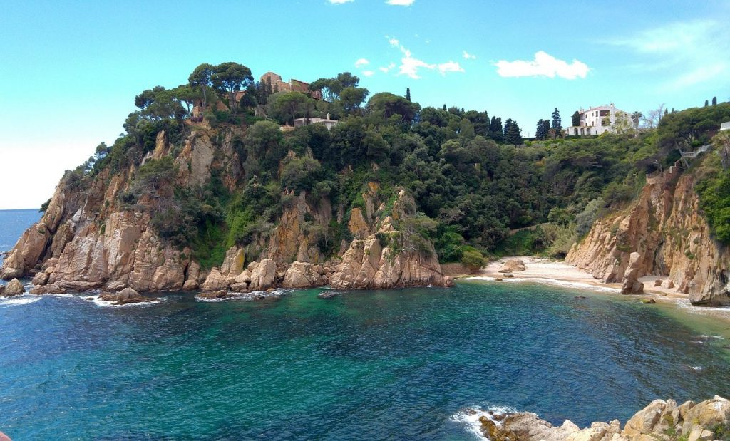 eine kleine Felsenbucht mit zwei großen Villen oben und tiefblauem Meer unten