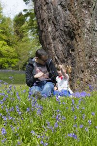 ein Mann mit Sonnenbrille und ein kleines Mädchen die unter einem Baum in einer grünen Wiese mit lila Blumen sitzen und sich gegenseitig mit Grashalmen kitzeln
