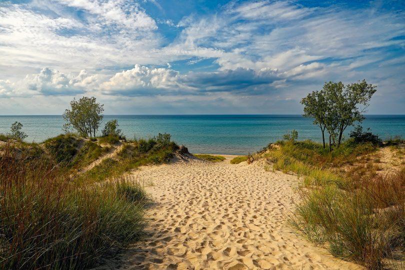 der zum Strand über eine Santdüne mit kleinen grünen Büschen an den Seiten
