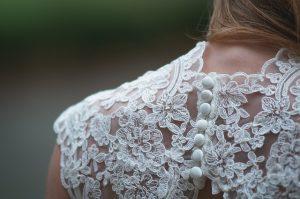 eine Frau die ein weisses Brautkleid trägt, zu sehen ist der hintere Schulterteil aus Spitze mit kleinen runden Stoffknöpfen