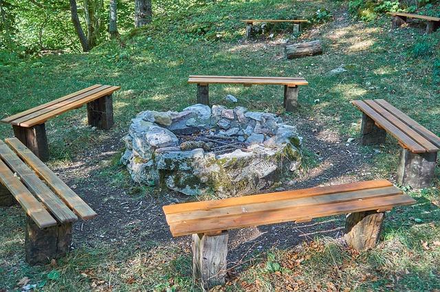 eine Feuerstelle aus Stein im Wald drum herum sind im Kreis fünf Holzbänke aufgestellt