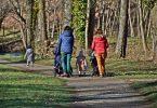 eine gepflasterter Weg der durch eine Park führt und auf dem zwei Frauen, eine mit blauer Jacke und die andere mit roter Jacke , jeweils einen Kinderwagen anschieben und zwischen ihnen und etwas weiter vor ihnen zwei kleine Kinder laufen