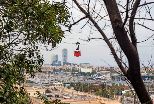 zwischen Baumästen ist über der Stadt Barcelona ein roter Wagon der Seilbahn zu sehen