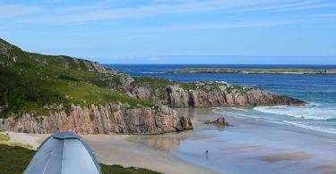 vorne links ein graues Zelt rechts Strand und Meer, grosse Klippen und zwei personen die am Strand entlang spazieren