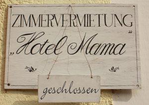 helles Holzschild auf dem steht Zimmervermietung Hotel Mamma und ein kleineres darunter auf dem steht geschlossen