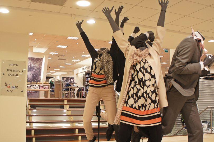 die Insel eines Einkaufszentrums auf dem zwei Mannequin die arme in die Lucht heben, sie sind herbstlich gekleidet und weiss, blau und orange